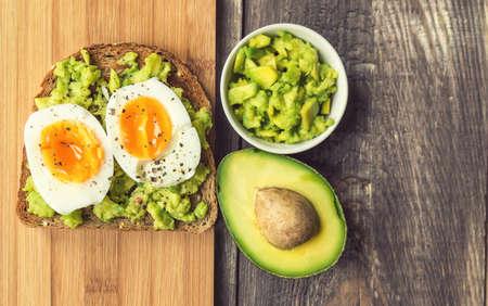 Pane tostato con l'avocado e l'uovo su fondo rustico di legno