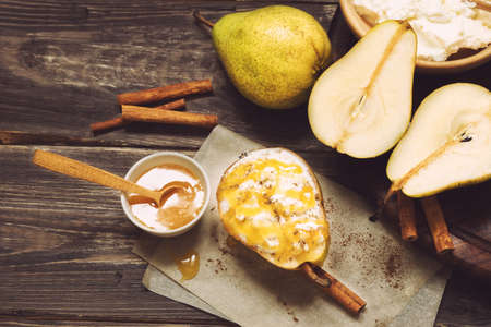 Pear with ricotta cheese, honey and cinnamon on rustic wooden background. Healthy and diet food. Top view. Stock Photo