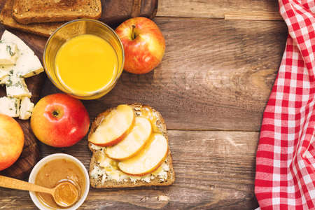 apple and honey: Toast with apple, honey and gorgonzola cheese on rustic wooden background. Healthy breakfast.