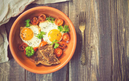 old fashioned vegetables: Fried eggs with cherry tomatoes and parsley in clay dish on rustic wooden background. Vintage toned picture. Stock Photo
