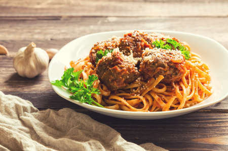 linguine pasta: Linguine pasta with meatballs in tomato sauce and parsley on rustic wooden background. Selective focus. Stock Photo