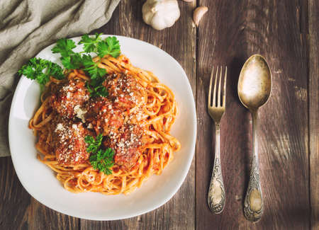 linguine pasta: Linguine pasta with meatballs in tomato sauce and parsley on rustic wooden background. Top view.