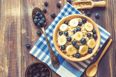 oatmeal: Oatmeal with blueberries and banana in wooden bowl on rustic wooden background. Healthy breakfast. Top view. Stock Photo