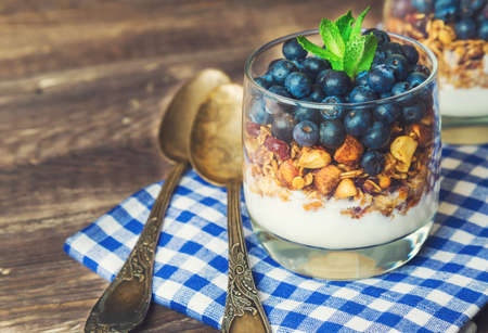 Homemade granola; muesli with blueberry and yogurt in glasses on rustic wooden background. Healthy breakfast.