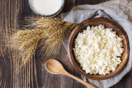 milk products: Cottage cheese, milk and ears of wheat on rustic wooden background. Dairy products for jewish holiday Shavuot. Top view.