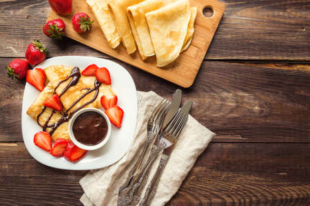 blini: Fresh homemade crepes with strawberries and chocolate sauce on rustic wooden background. Top view.