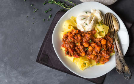 Pappardelle pasta with meat ragout with pumpkin and burrata cheese on gray concrete background. Italian cuisine. Top view.