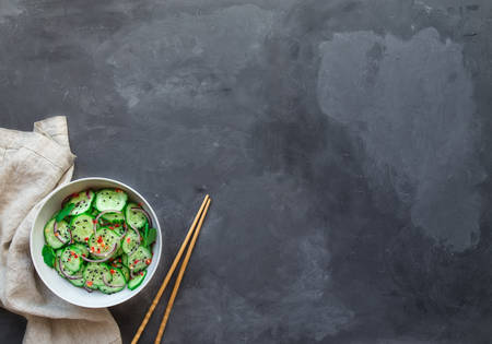 Asian cucumber salad with red onion, chilli pepper and black sesame in white bowl on gray concrete