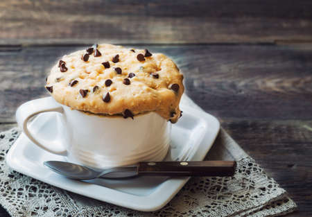 Fresh homemade cake in mug with peanut butter and chocolate chips on rustic wooden Banco de Imagens