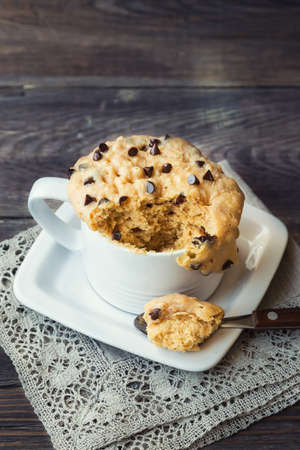 Fresh homemade cake in mug with peanut butter and chocolate chips on rustic wooden 写真素材