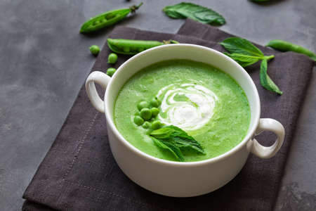 Green pea and mint soup in bowl on gray concrete
