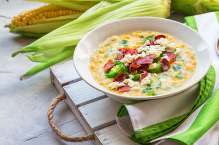 Fresh homemade corn soup with bacon, jalapeno and goat cheese in bowls on light gray concrete