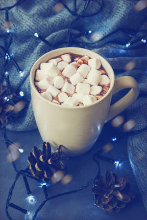 Hot winter drink with cocoa and marshmallows in mug on concrete  with Christmas garland and pine cones.
