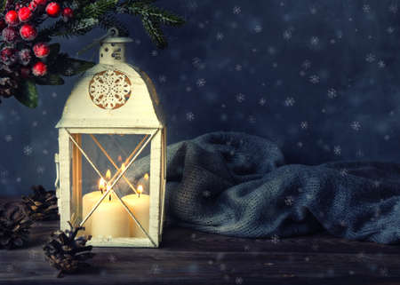 Lantern with burning candles with Christmas decorations and pine cones. Фото со стока