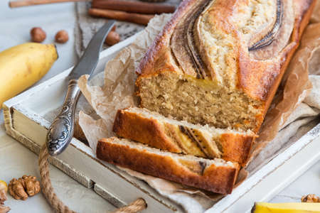 Fresh homemade banana bread in white wooden tray with ingredients on light concrete