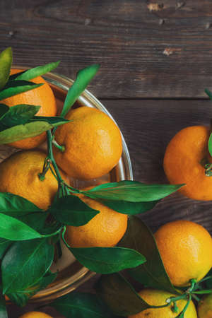 Fresh organic tangerines with leaves on rustic wooden