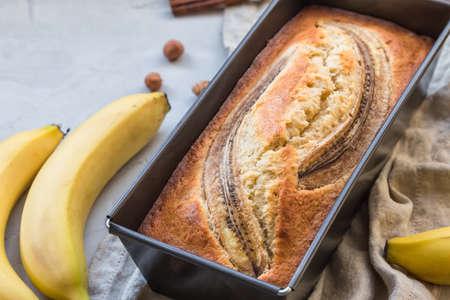 Fresh homemade banana bread in baking form on light concrete background.