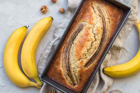 Fresh homemade banana bread in baking form on light concrete background. Top view. Фото со стока