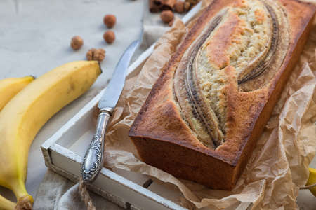 Fresh homemade banana bread in white wooden tray with ingredients on light concrete background. Фото со стока