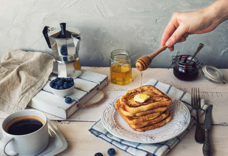 French toasts with butter and blueberries for breakfast. Hand is pouring honey on the top. Фото со стока