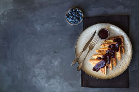 French toasts with blueberry jam on gray concrete