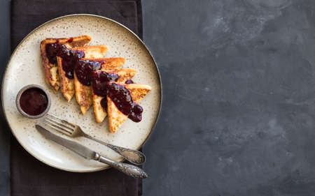 French toasts with blueberry jam on gray concrete background. Top view. Space for text.