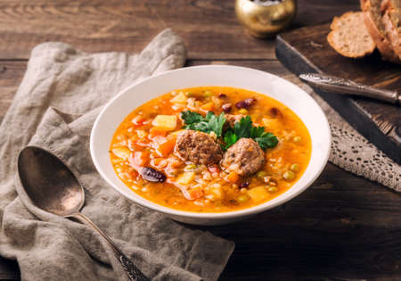 Homemade vegetable soup with meatballs and slices of bread on rustic wooden background.