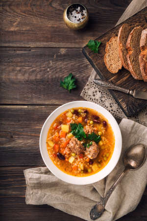 Homemade vegetable soup with meatballs and slices of bread on rustic wooden background. Top view.
