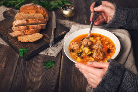 Cropped view of woman eating vegetable soup with meatballs at rustic wooden table.