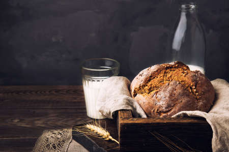 Homemade rustic rye bread with coriander seeds and a bottle of milk on old wooden table. Rural food still life.