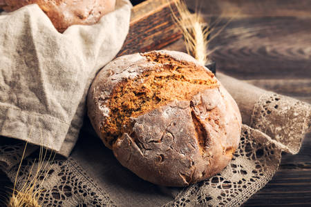 Homemade rye bread with coriander seeds on rustic wooden background. Rural food still life. Фото со стока