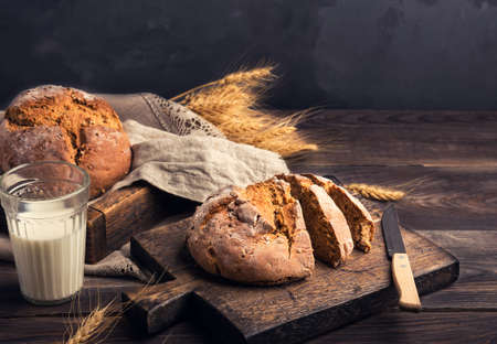 Homemade rustic rye bread with coriander seeds on wooden cutting board. Rural food still life. Фото со стока