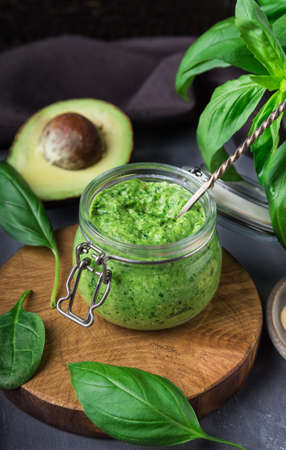 Fresh homemade vegan pesto sauce with basil, spinach, cashew nuts and avocado in jar on gray concrete