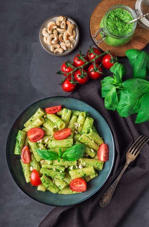 Fresh homemade tortiglioni pasta with vegan pesto sauce, cashew nuts and cherry tomatoes on gray concrete