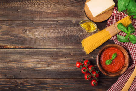 Homemade marinara sauce, spaghetti pasta, parmesan cheese, olive oil, basil and cherry tomatoes on rustic wooden background. Traditional italian cuisine ingredients. Top view. Space for text.