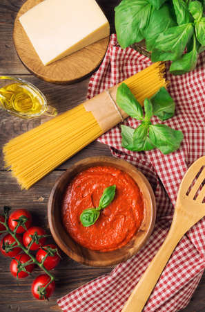 Homemade marinara sauce, spaghetti pasta, parmesan cheese, olive oil, basil and cherry tomatoes on rustic wooden background. Traditional italian cuisine ingredients. Top view. Фото со стока