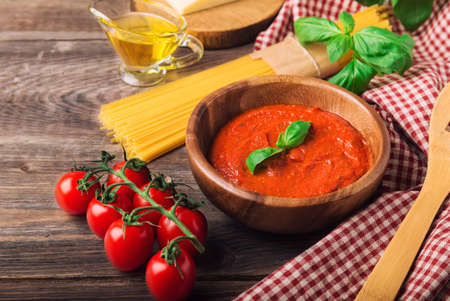 Homemade marinara sauce, spaghetti pasta, parmesan cheese, olive oil, basil and cherry tomatoes on rustic wooden background. Traditional italian cuisine ingredients. Фото со стока