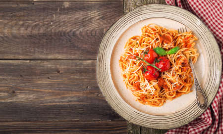 Spashetti pasta with tomato sauce and baked tomatoes cherry on rustic wooden background. Italian cuisine. Top view. Space for text. Фото со стока