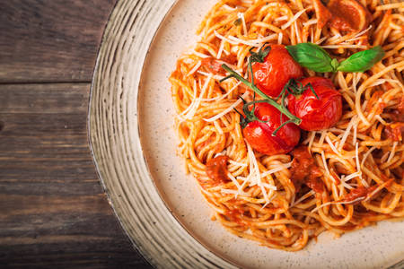 Spashetti pasta with tomato sauce and baked tomatoes cherry on rustic wooden background. Italian cuisine. Top view. Close-up.