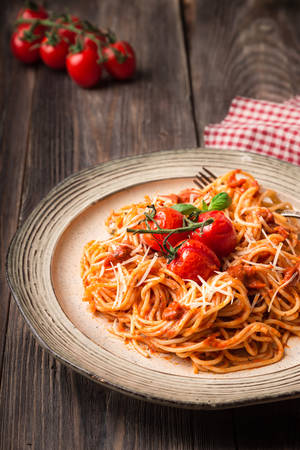 Spashetti pasta with tomato sauce and baked tomatoes cherry on rustic wooden background. Italian cuisine.