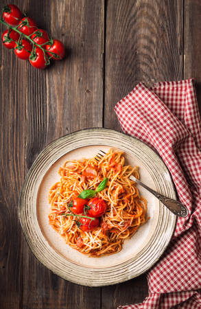 Spashetti pasta with tomato sauce and baked tomatoes cherry on rustic wooden background. Italian cuisine. Top view.