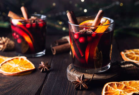 Christmas mulled wine with cranberries, orange and spices on rustic wooden background. Traditional hot winter drink.