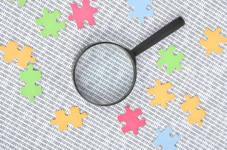 Puzzle and binary code with magnifier photo