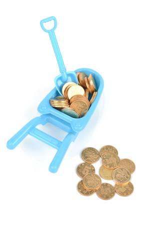 carretilla de mano: Toy carretilla de mano y las monedas Foto de archivo