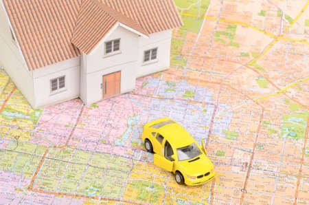 Toy car and house model on map photo