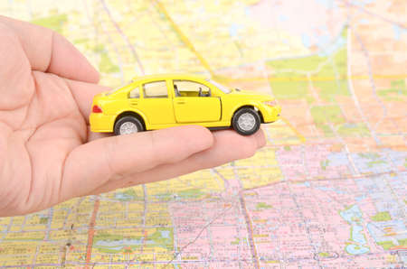 Toy car and map with finger photo