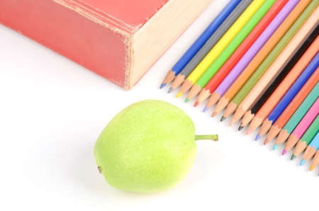 Pear and color pencils with book photo