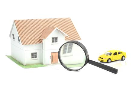 Toy car and house with magnifier photo