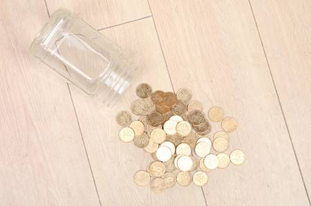 Coins in glass jar on floor photo