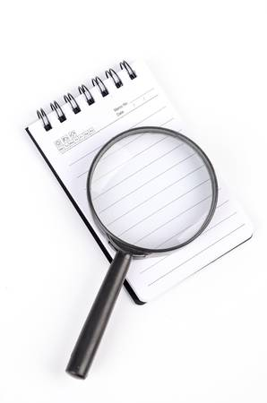 investigating: Magnifier and notepad Stock Photo